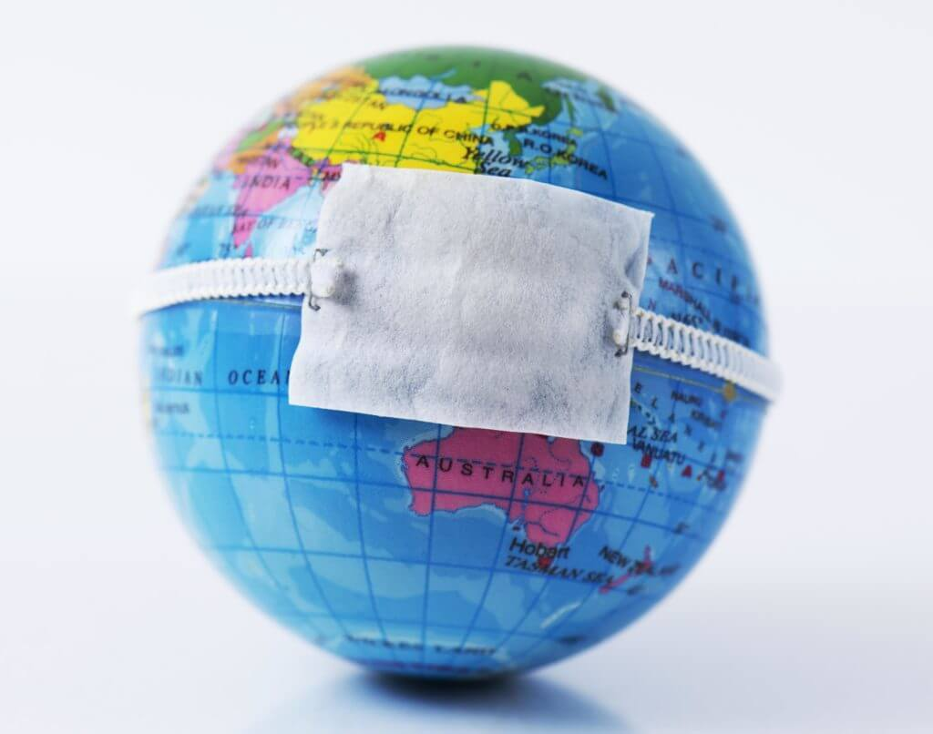 closeup of a terrestrial globe with a protective mask placed over China, depicting the recent coronavirus outbreak, with a blank space on top