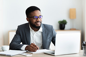 Handsome black entrepreneur using laptop and taking notes while working in modern white office, panorama